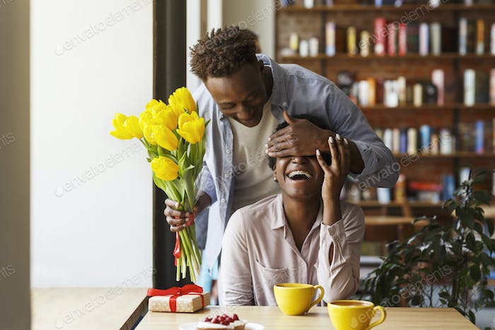 African American guy giving flowers to his girlfriend in urban cafe