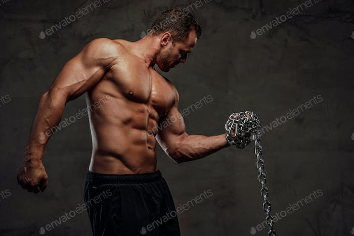 Strong guy holding chains and posing in background