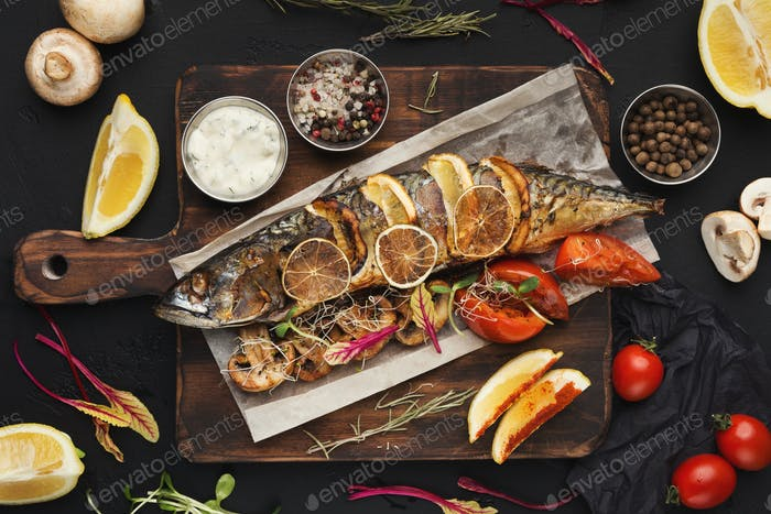 Grilled fish on wooden board at restaurant table