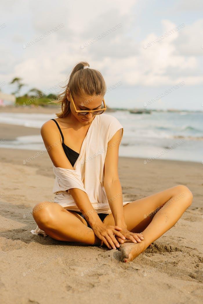 Hübsche Frau spielen mit Sand an der Küste.