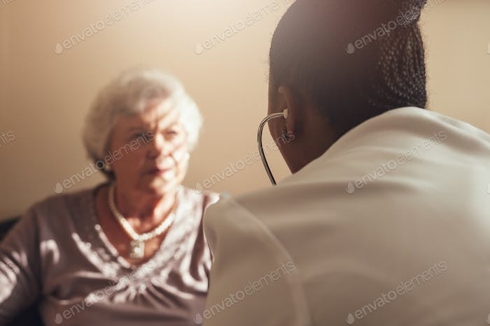 Female doctor examining senior patient