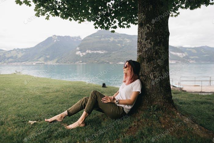 junge Frau mit Hut und Sonnenbrille sitzt und lehnt am Baum nahe dem schönen Bergsee in Bern,