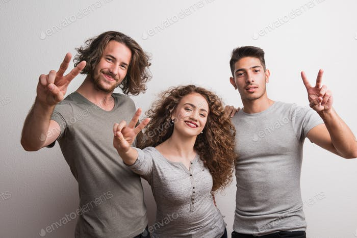 Portrait of joyful young girl with two boy friends standing in a studio, V for victory.