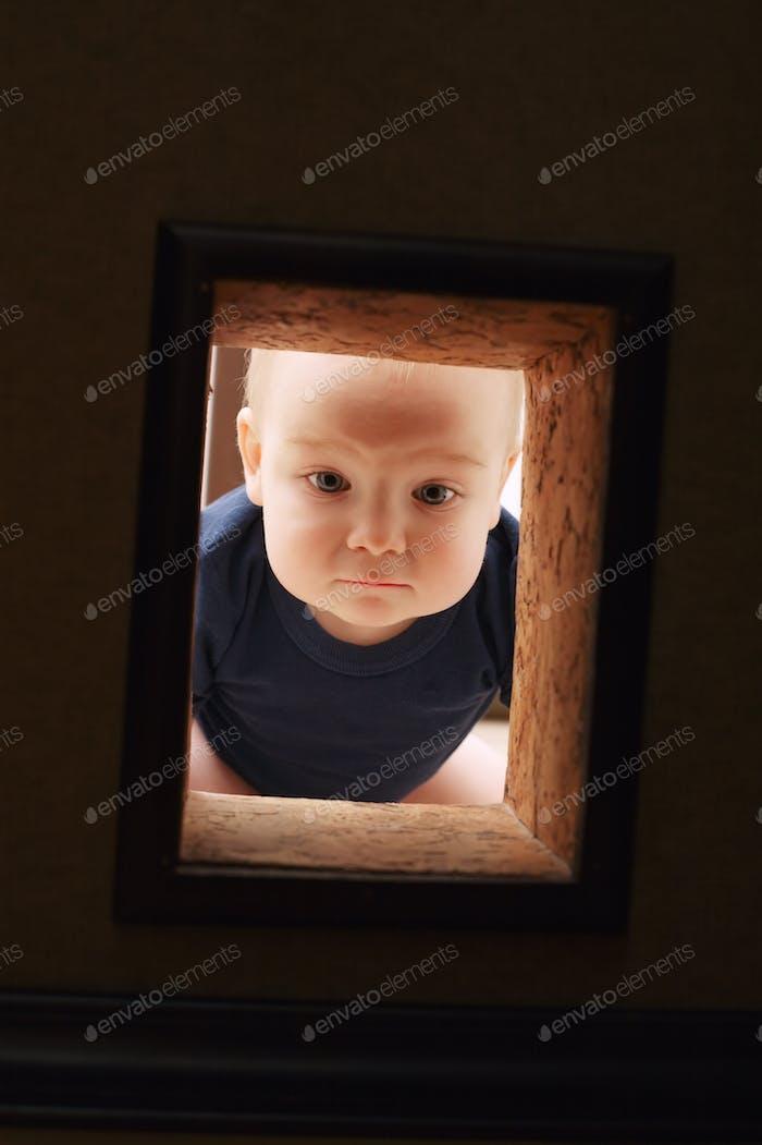 Kleines Kind sieht in die Wand zu Loch