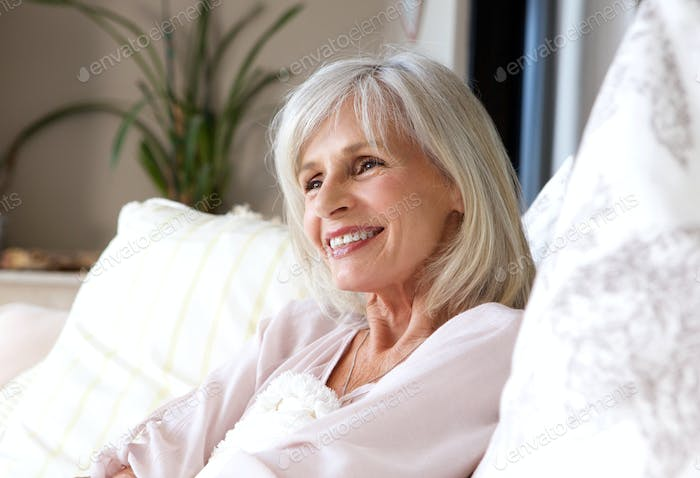 happy older woman sitting on couch relaxed and smiling