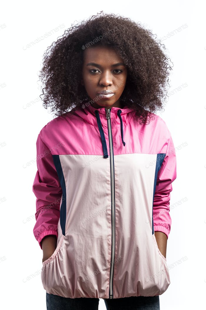 Young curly brown-haired girl dressed in the pink sport jacket stands at the white background in the