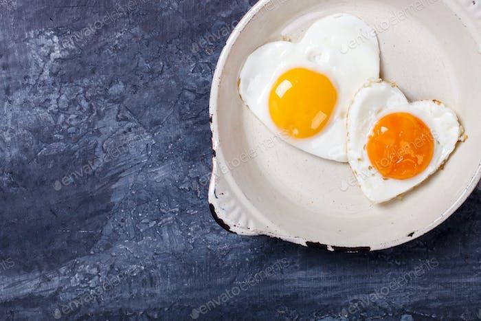 Fried egg in heart shape.Holiday Breakfast.Valentin Day.