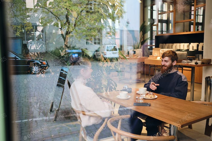 Young beautiful couple happily talking during coffee break in cafe