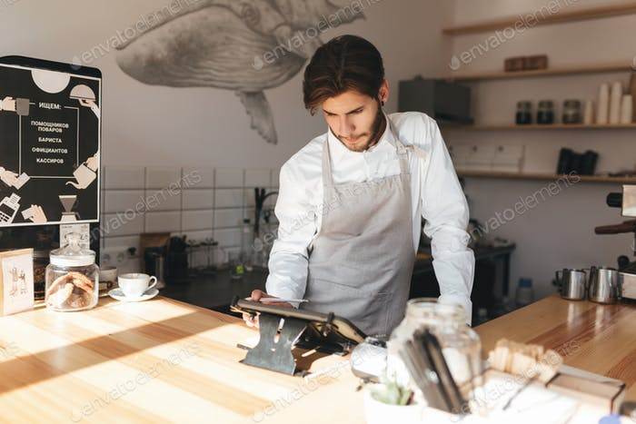 Thoughtful man working with terminal at the counter on his workplace in restaurant