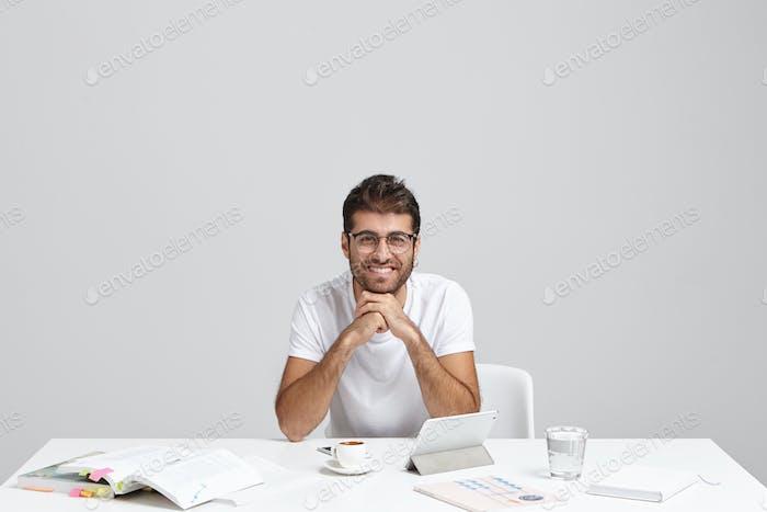 Intelligenter junger Mann mit ansprechendem Aussehen sitzt drinnen am weißen Tisch, umgeben von Documen