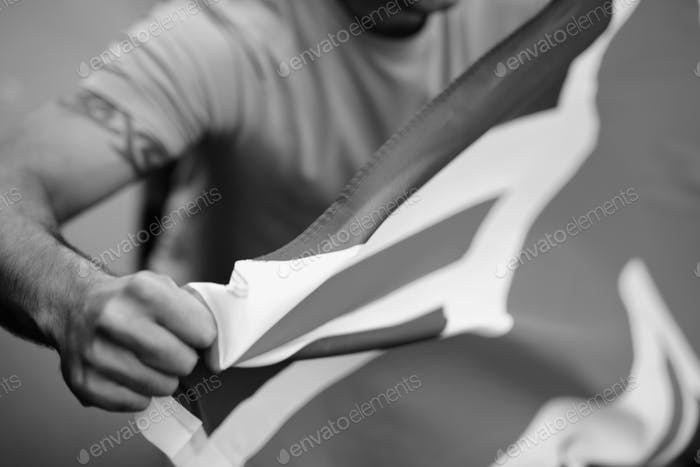 Close up of a man holding the flag of England