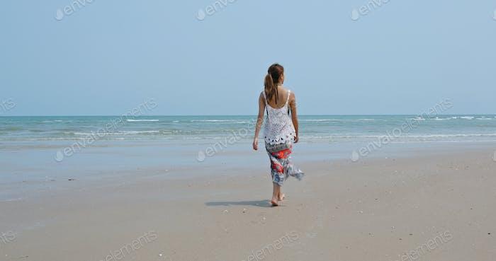 Asian woman walk on the beach