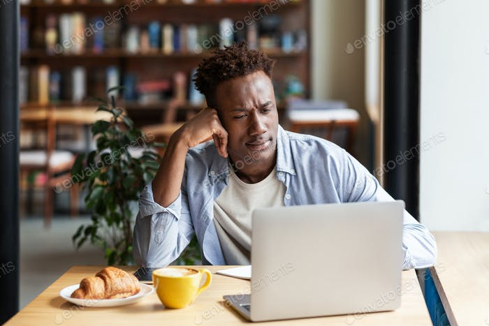 Online education. Focused black guy studying for difficult exam on laptop at coffee shop