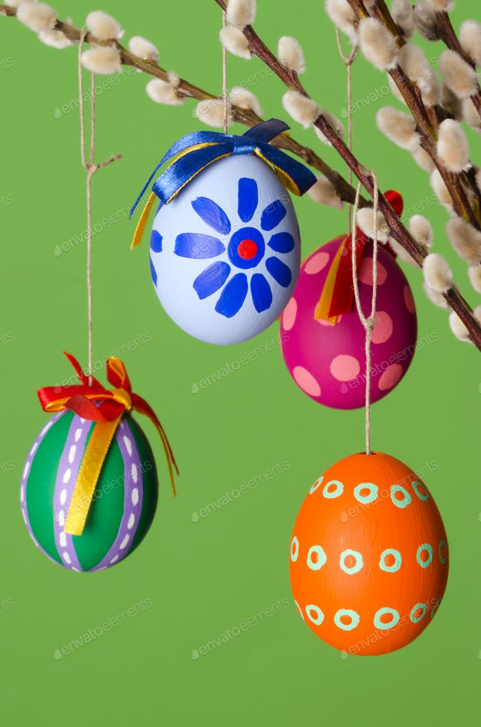 Paschal eggs on willow bouquet, vertical over green