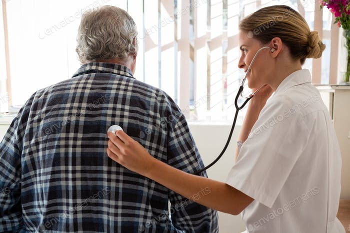 Female doctor examining senior patient with stethoscope at nursing home