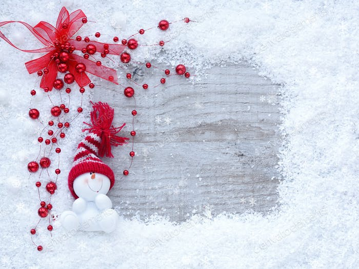 Frame of snow with snowmen on wooden background with space for y