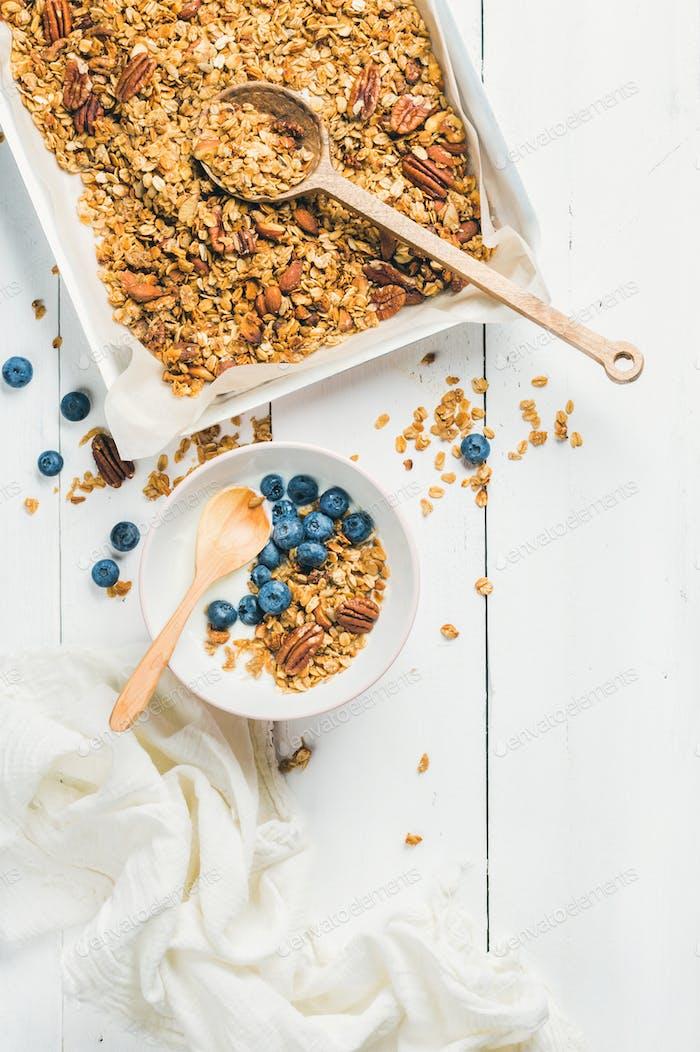 Hafermüsli mit Pekannüssen, Mandeln, Joghurt und Heidelbeere in Schüssel