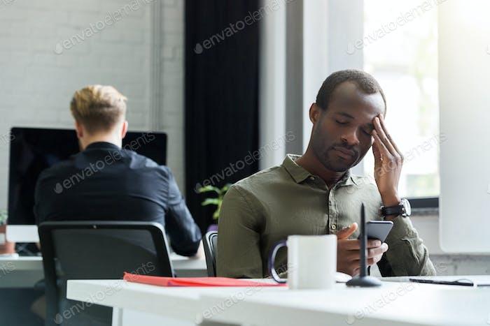 Tired afro american man having a headache