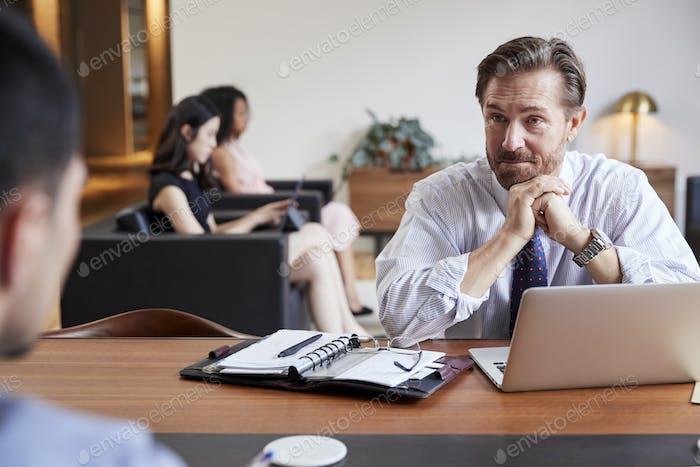 Geschäftsmann an einem Schreibtisch Blick auf einen Kollegen gegenüber