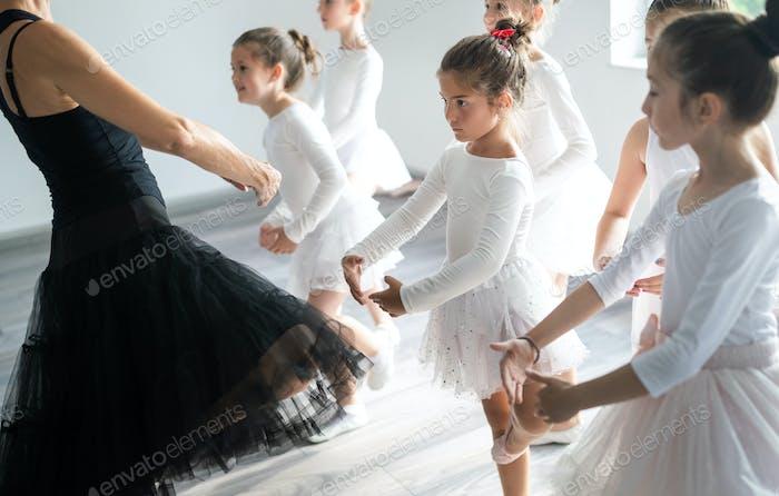 Ballet teacher and students ballerinas exercising in dance class in school