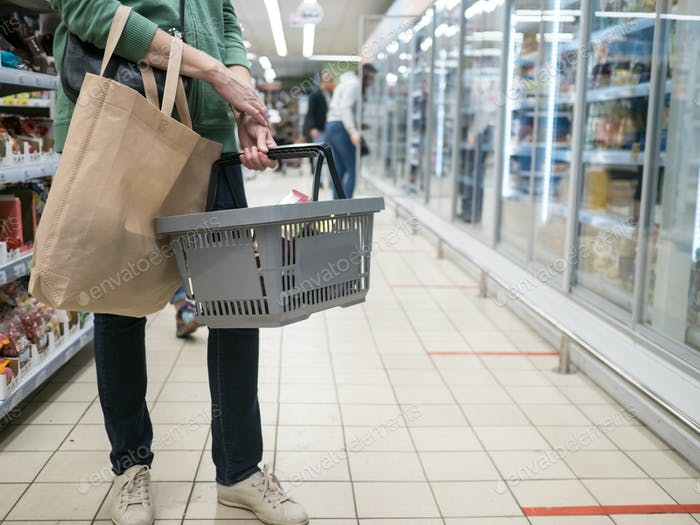 Woman with a shopping basket at a grocery store
