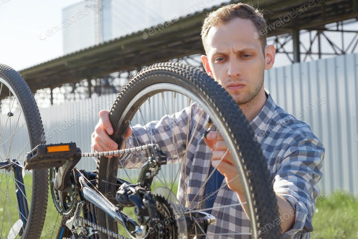 A concentrated craftsman is diagnosing bike malfunctions on the street.