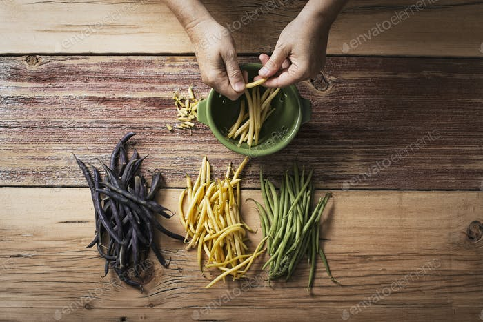 Green, yellow and black haricot beans, fresh vegetables being prepared by a person.