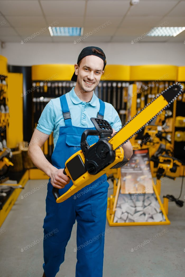 Male worker holds chainsaw in tool store