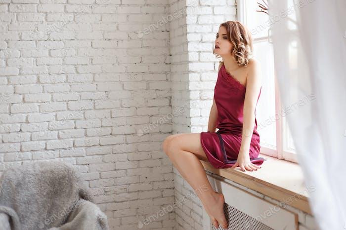 schöne einsame junge rothaarige Frau in einem roten Kleid sitzt auf einer Fensterbank