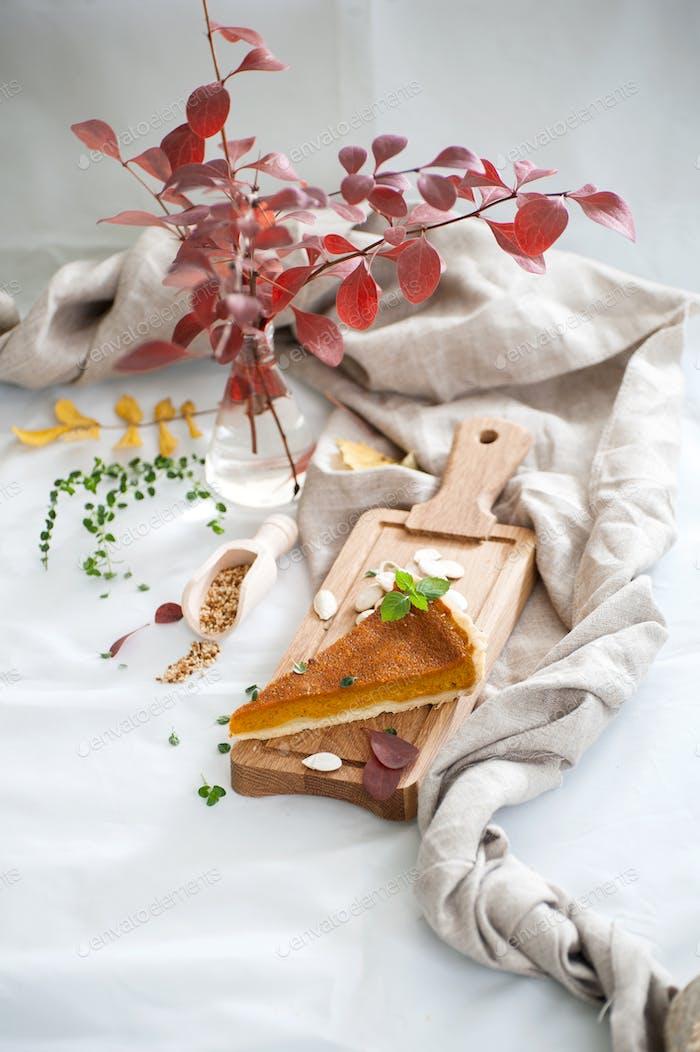 A piece of pumpkin pie on a wooden board.