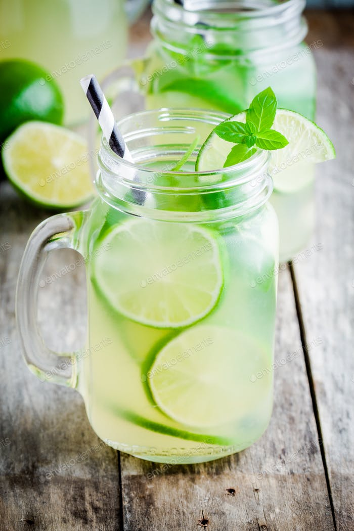 homemade lemonade with lime, mint in a mason jar on a wooden table
