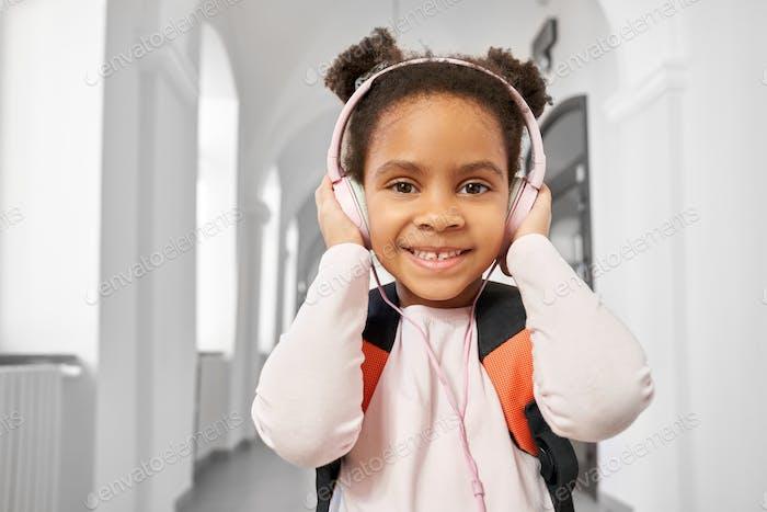 Portrait of schoolgirl with headphones in school