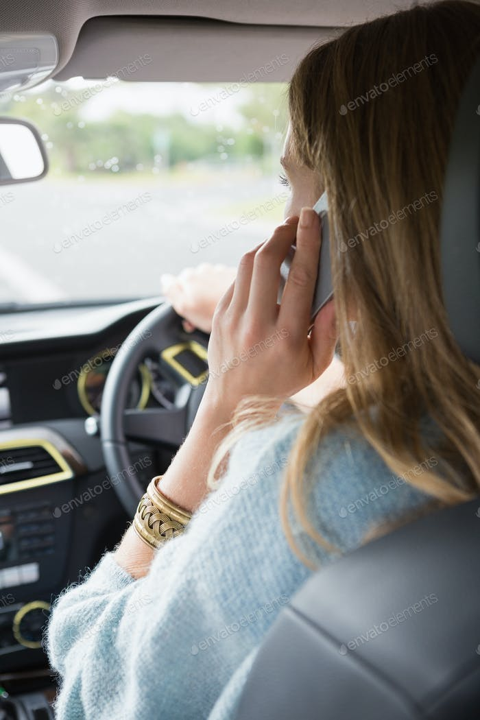 Young woman on the phone in her car