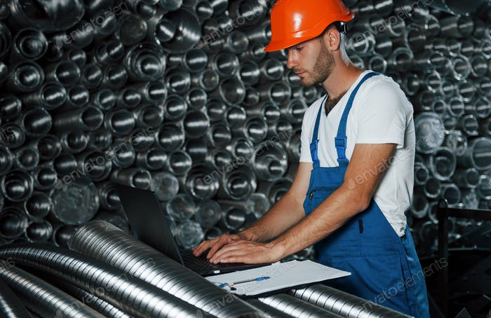 Using laptop. Man in uniform works on the production. Industrial modern technology