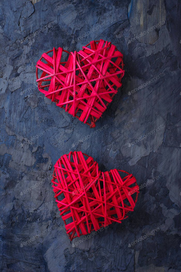 Two red hearts on concrete background