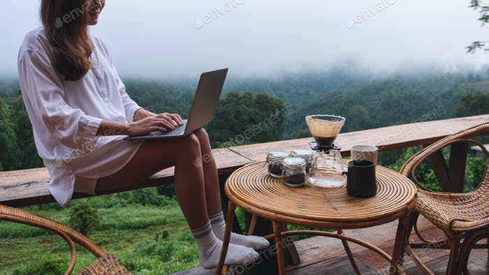 A woman using and working on laptop computer while sitting on balcony with a beautiful nature view