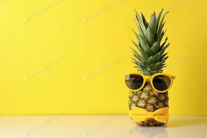 Pineapple with tie bow and sunglass against yellow background