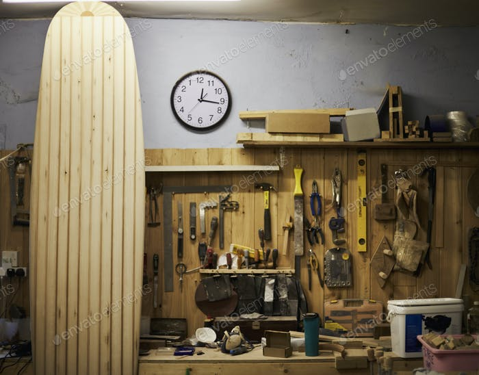 A tall wooden surfboard propped up in a workshop.