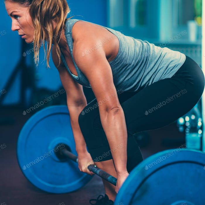 Female athlete lifting weights in the gym
