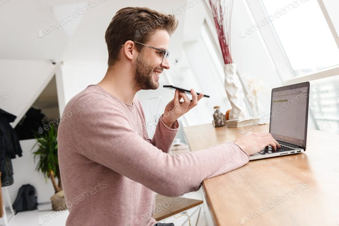 Image of young man working on laptop and using cellphone in cafe