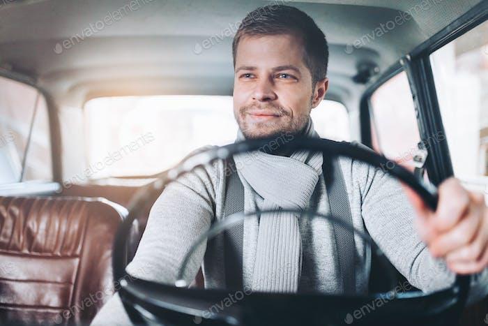 Handsome man sitting inside his vintage car