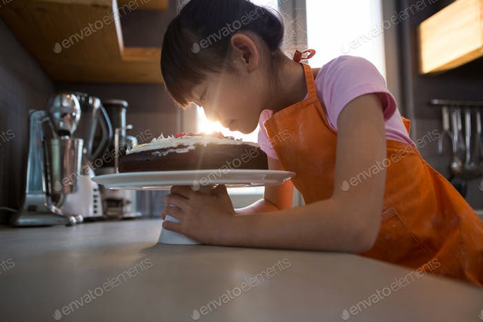 Girl looking at cream cake in kitchen