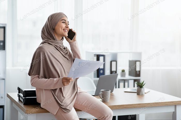 Happy Female Entrepreneur Talking On Mobile Phone And Holding Financial Reports