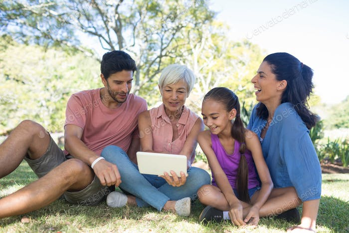 Family looking at digital tablet in the park
