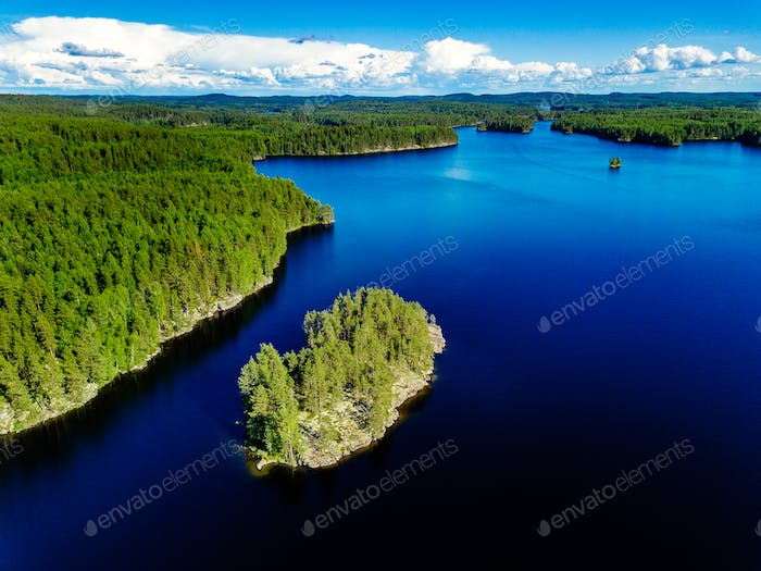 Aerial view of blue lake and green forest. Beautiful summer landscape in Finland.