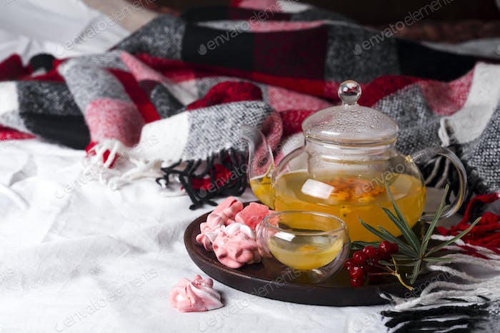 tray with honey and a cup of hot tea with pink meringues in the bed,