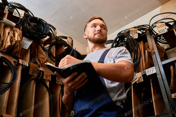 Mechanic Reviewing Stock in Storage Room