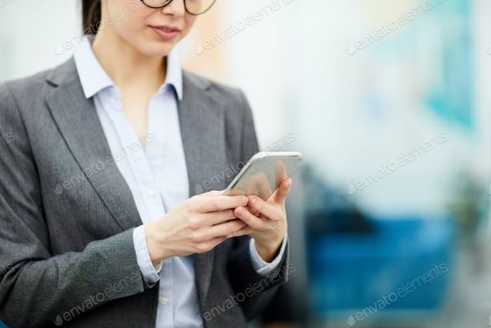 Unrecognizable Businesswoman Using Smartphone