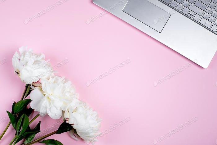 Flat lay home office desk. Female workspace with laptop, white peony bouquet. Top view, copy space