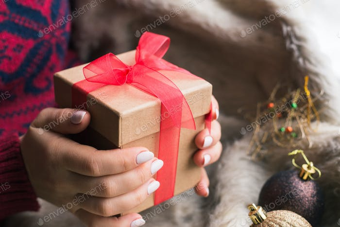 A woman holding a Christmas gift with a red ribbon on a wooden table. Christmas presents